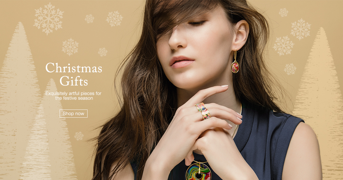 Christmas Gifts. Brown-haired woman in a blue top, wearing Paul Gauguin collection earings, rings and pendant. Click to explore the Christmas Gift section.