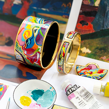 Hommage á Paul Gauguin Tahiti jewellery pieces laying next to sketches of the design and color tubes with pink and yellow color and a little pot for color mixing.