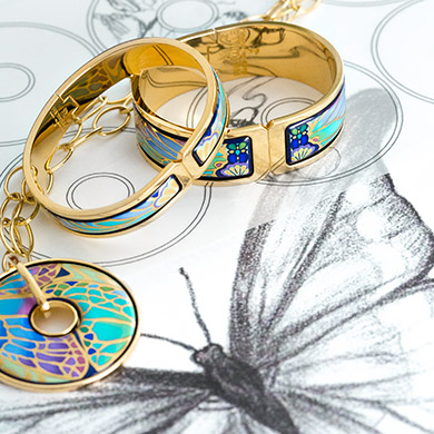 Hommage á Alphonse Mucha Papillon Clasp Bangles, Luna Piena pendant laying on pencil sketches of the design