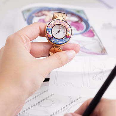 Hand holding a Jewellery Watch Helena from the Hommage á Claude Monet Orangerie Rosé collection and the other hand painting a sketch of the design.