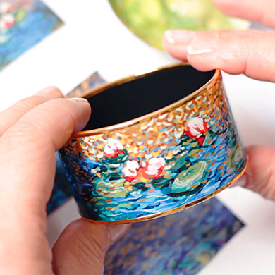 Hands holding a Bordered Bangle Diva from the Hommage á Claude Monet Orangerie collection.