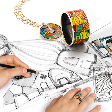 Hommage á Hundertwasser Street Rivers Bordered Bangle Diva and Luna Piena Pendant laying on sketches of the design. A woman is painting them.