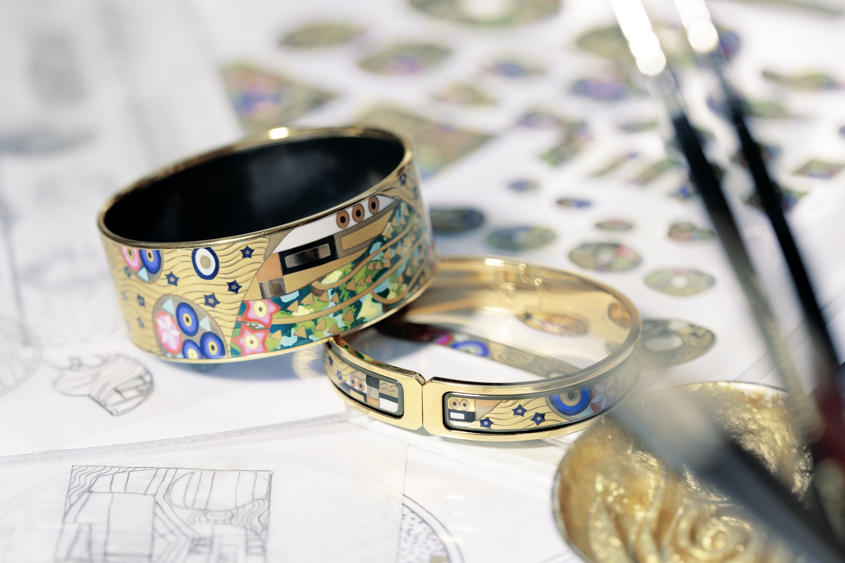 Hommage á Gustav Klimt The Ultimate Kiss Clasp Bangle Ballerina and Bordered Bangle Donna laying on sketches of the design, next to a little pot of golden color and three brushes.