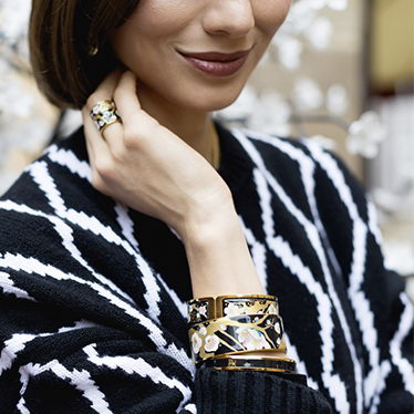 Brunette Woman with short hair and a black and white wool jumper wearing the Hommage á Vincent van Gogh L'amandier Noir Ring Diva, Bordered Bangle Donna, Ballerina and Monochrome Bangle in black.