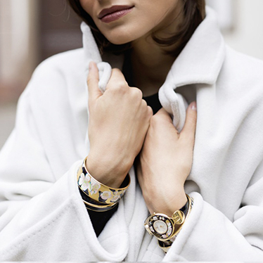 Brunette Woman with short hair and light grey woolen coat wearing the Hommage á Vincent van Gogh  L'amandier Noir Jewellery Watch and Bordered Bangle Miss.