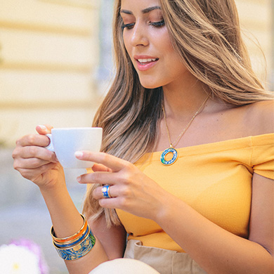 A blonde woman in a yellow top is holding a coffee cup and wearing Hommage á Vincent van Gogh Éternité Pendant Helena, Bordered Bangle Donna, two Monochrome Bangles in orange and blue and Ring Diva.