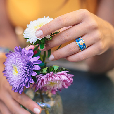 A woman is holding white, pink and lilac flowers while wearing Hommage á Vincent van Gogh Éternité Ring Diva.