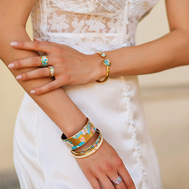 Brunette woman in a white shirt is wearing Bordered Bangle Mademoiselle from the Hommage á Vincent van Gogh collection L'Amandier turqoise and two Monochrome Bangles in turquoise and white.