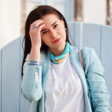 Brunette woman with long hair and a turquoise blazer and white t-shirt is wearing Monochrome Bangle in blue, Ring Diva and Bordered Bangle Ballerina and Earrings Mini Creoles from the Hommage á Hundertwasser Spiral of life collection in white gold and a scarf from the Hommage á Vincent van Gogh collection L'Amandier turquoise.