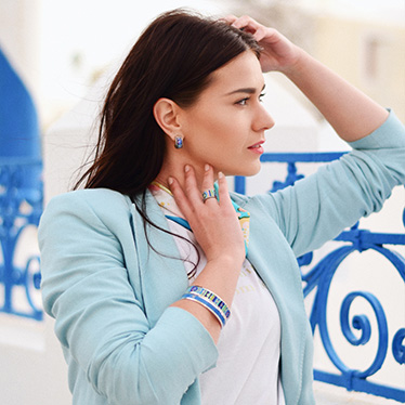Brunette woman with long hair and a turquoise blazer and white t-shirt is wearing Monochrome Bangle in blue, Ring Diva and Bordered Bangle Ballerina and Earrings Mini Creoles from the Hommage á Hundertwasser Spiral of life collection in white gold.