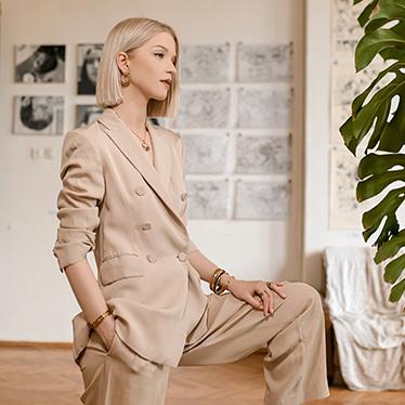 Blonde woman in a beige blazer wearing FREYWILLE jewellery