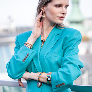 Blonde woman wearing a turquoise blazer and jewellery by FREYWILLE