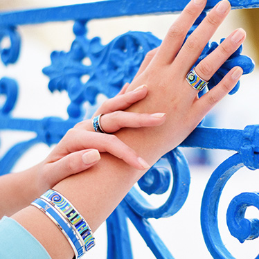 Woman is wearing Monochrome Bangle in blue, Ring Diva and Bordered Bangle Ballerina and Earrings Mini Creoles from the Hommage á Hundertwasser Spiral of life collection in white gold.