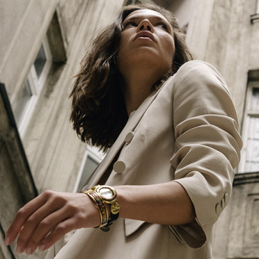 Brunette woman in a beige blazer wearing the Independent Collection Passionate Russia Jewellery Watch and Clasp Bangle Ballerina.